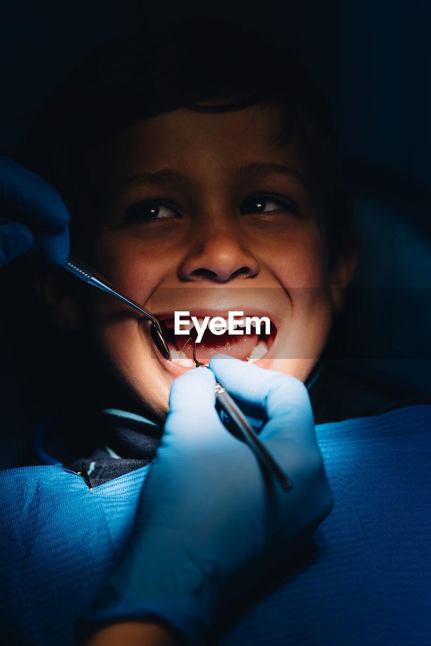 Dentist Operating Cheerful Boy In Medical Clinic