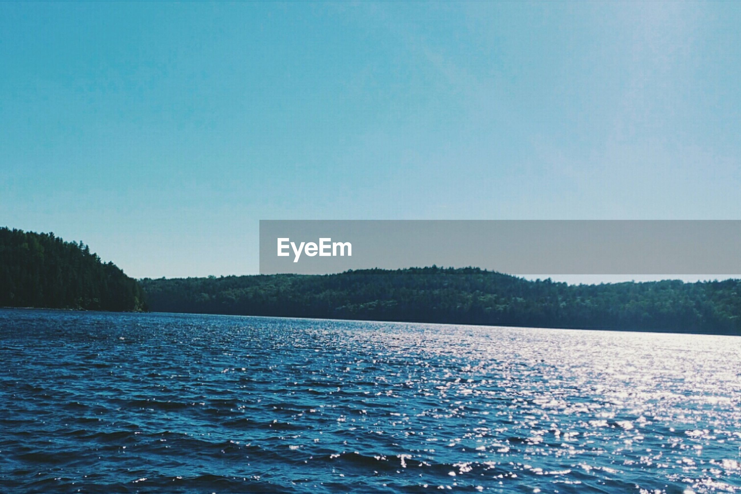 water, clear sky, waterfront, copy space, tranquil scene, scenics, tranquility, sea, beauty in nature, blue, rippled, nature, idyllic, mountain, outdoors, day, no people, lake, calm, remote