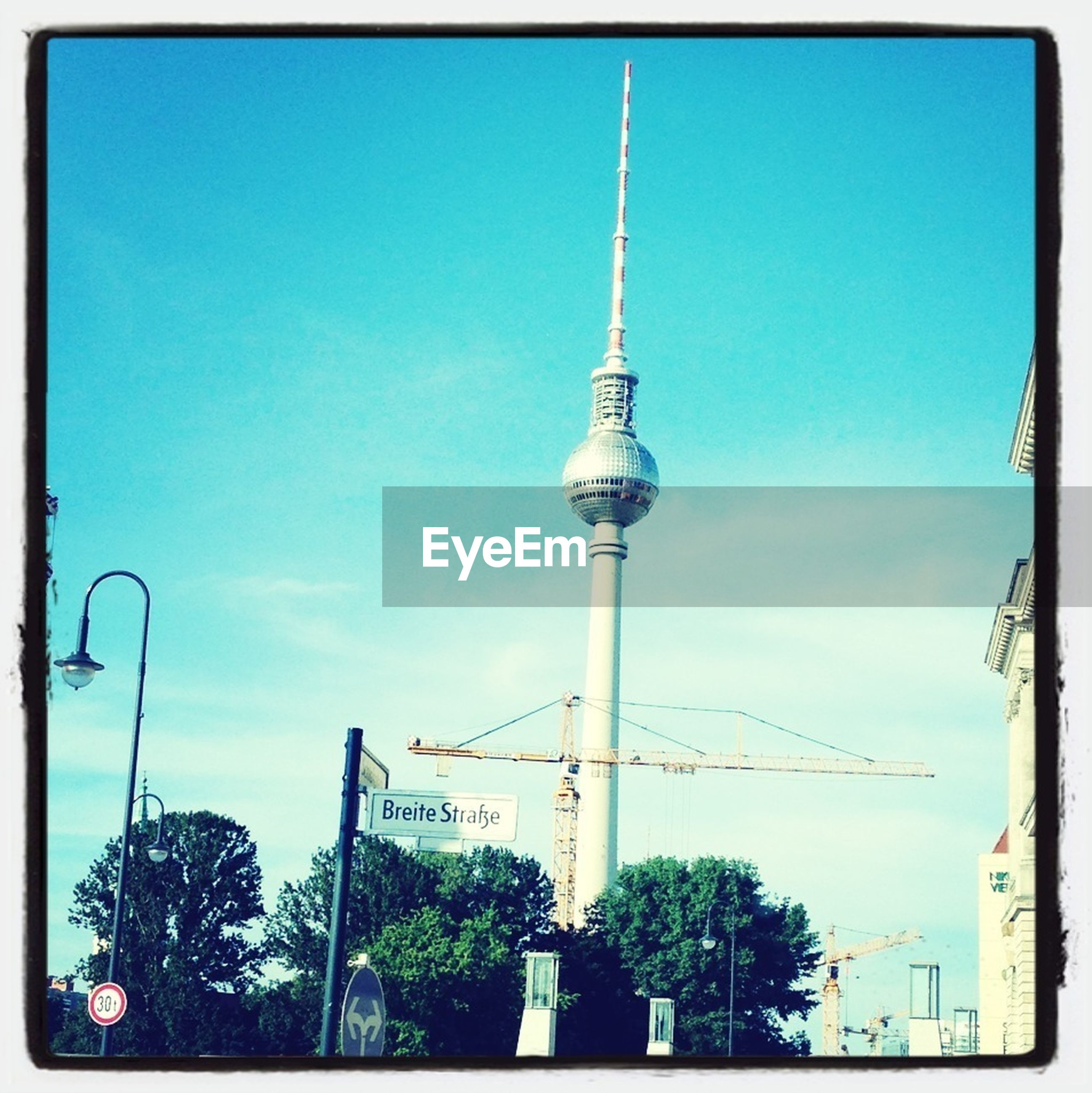 transfer print, communications tower, low angle view, built structure, architecture, blue, tree, tower, building exterior, street light, sky, auto post production filter, tall - high, communication, television tower, fernsehturm, spire, city, day, clear sky