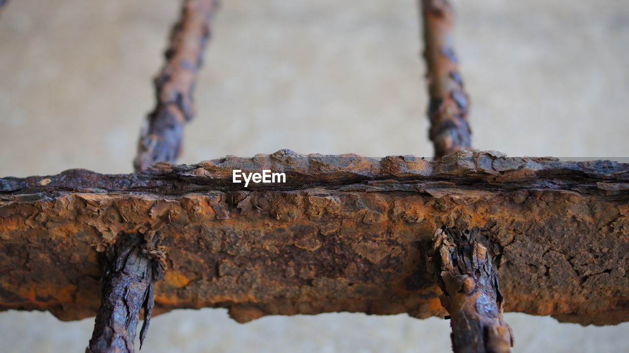 Low Angle View Of Rusty Metallic Gate Against Wall