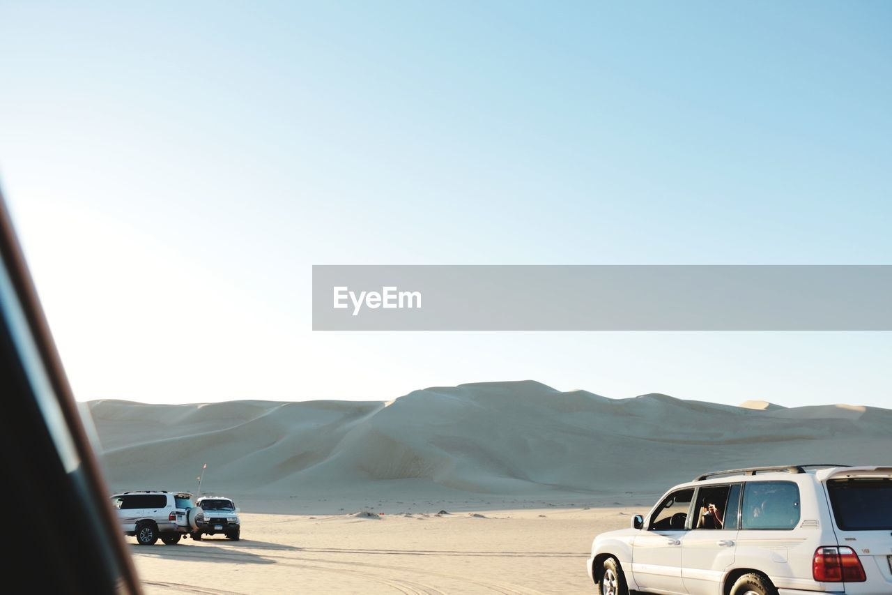 Off-Road Vehicles On Desert Against Clear Blue Sky