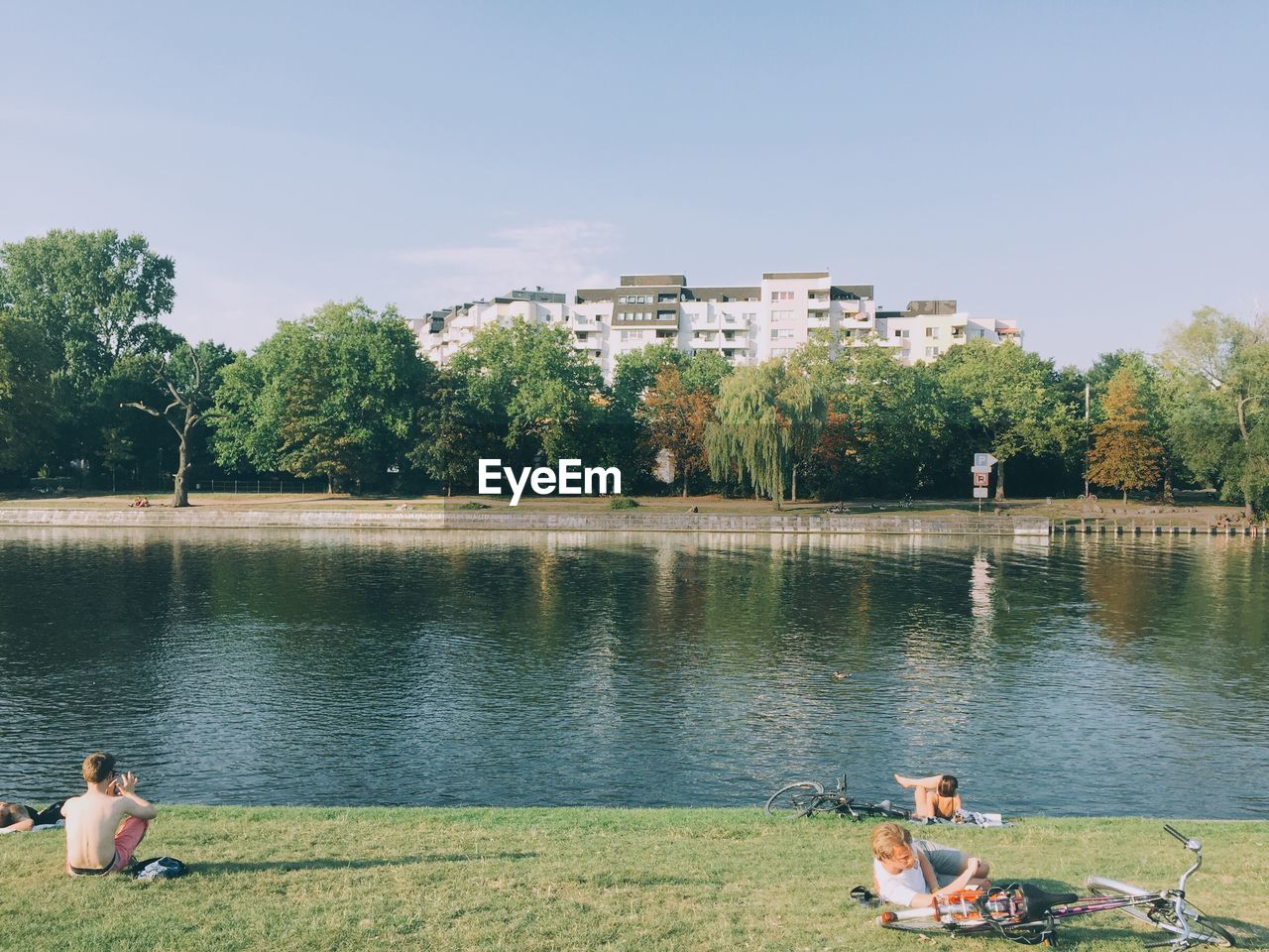 water, tree, lake, real people, day, leisure activity, togetherness, boys, outdoors, sitting, childhood, building exterior, nature, architecture, men, built structure, two people, lifestyles, grass, women, full length, sky, mammal, people