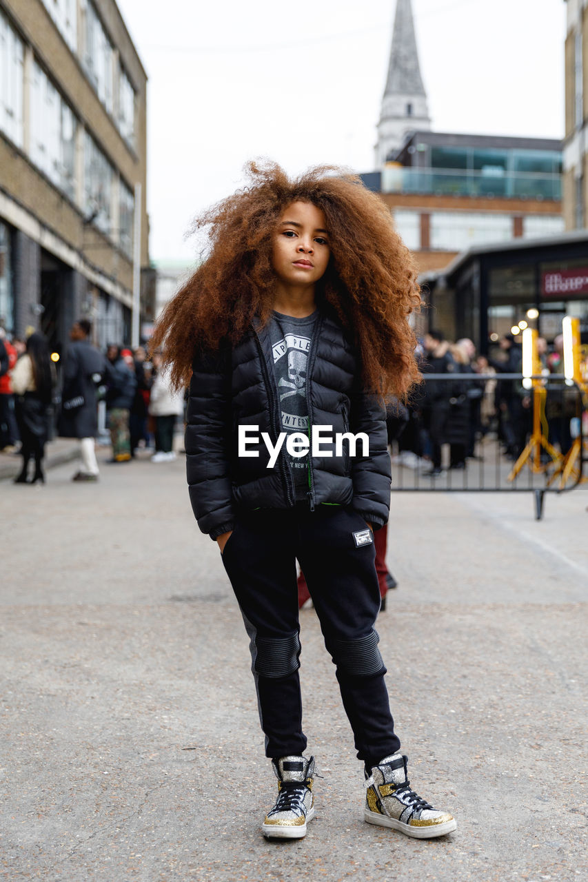 one person, lifestyles, portrait, full length, hair, standing, leisure activity, front view, hairstyle, architecture, looking at camera, young adult, real people, building exterior, curly hair, young women, built structure, long hair, city, beautiful woman, outdoors, warm clothing, teenager