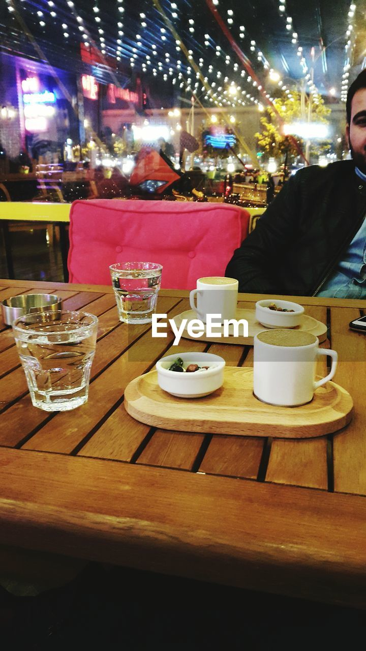 food and drink, table, restaurant, cafe, refreshment, drink, coffee cup, coffee - drink, sidewalk cafe, night, real people, food, illuminated, sitting, drinking glass, plate, indoors, one person, lifestyles, men, freshness, people