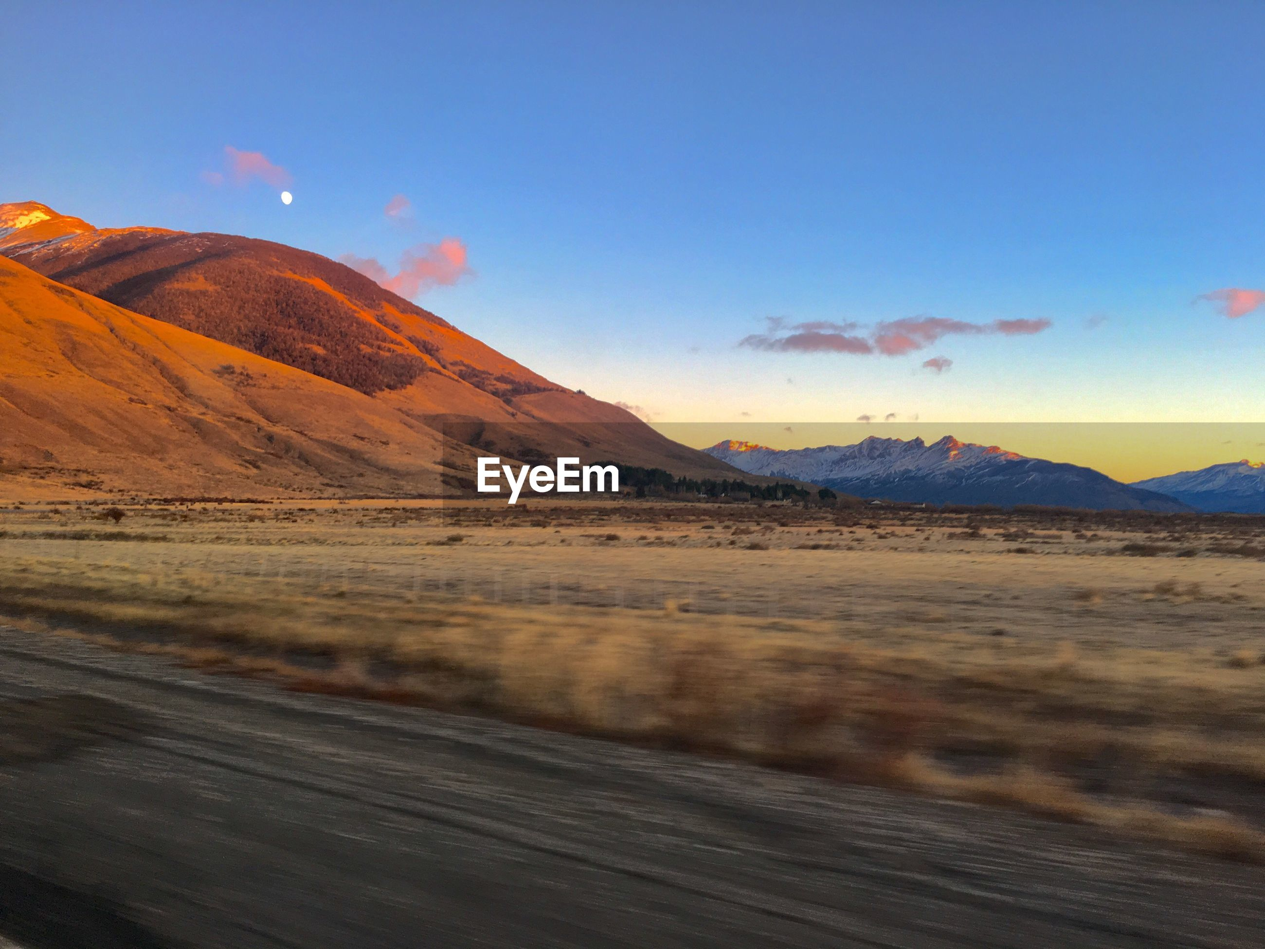 SCENIC VIEW OF ROAD BY MOUNTAINS AGAINST BLUE SKY