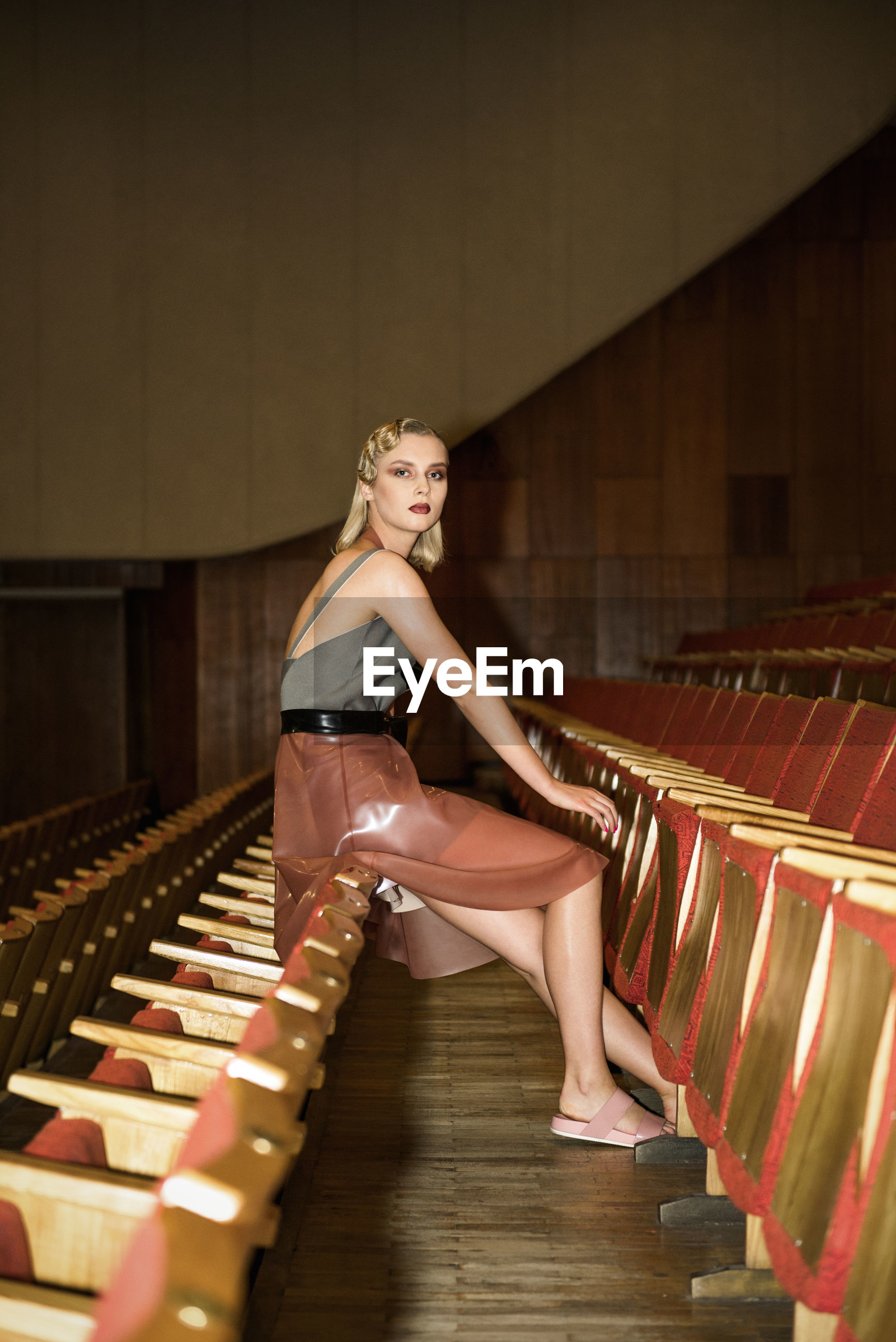 Side view portrait of young woman sitting on chair in auditorium