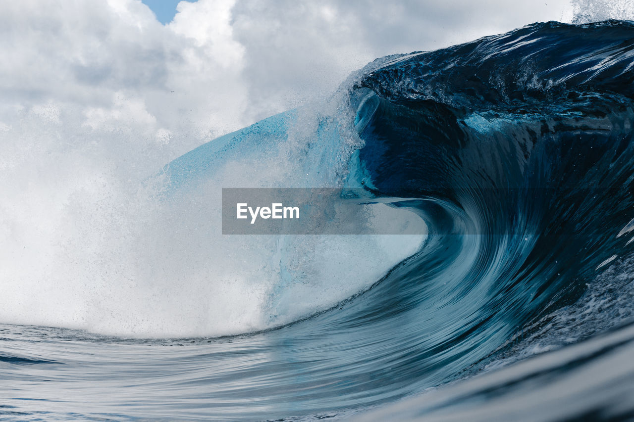 Close-up of wave splashing on shore against sky