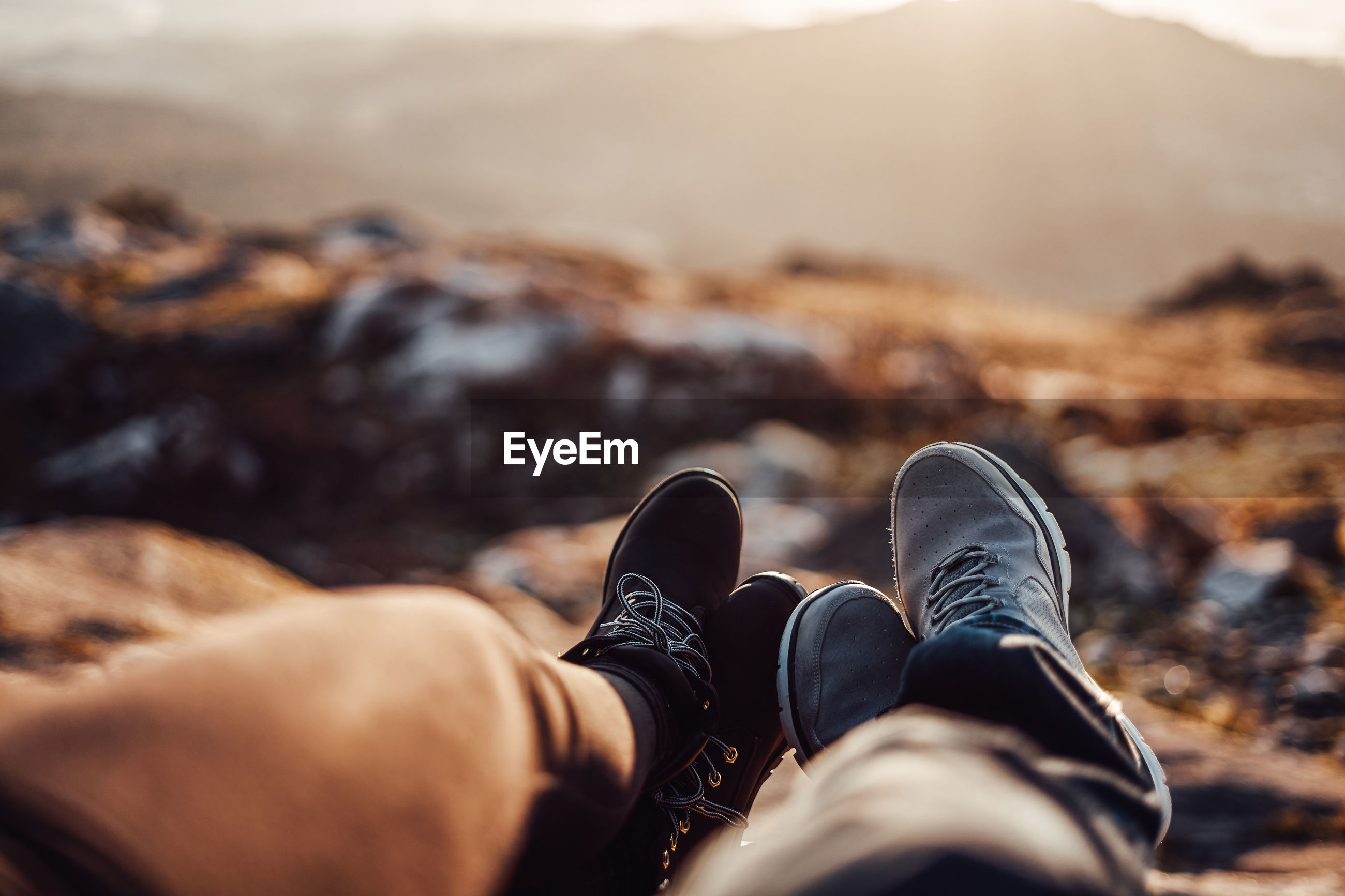 Low section of couple relaxing on mountain