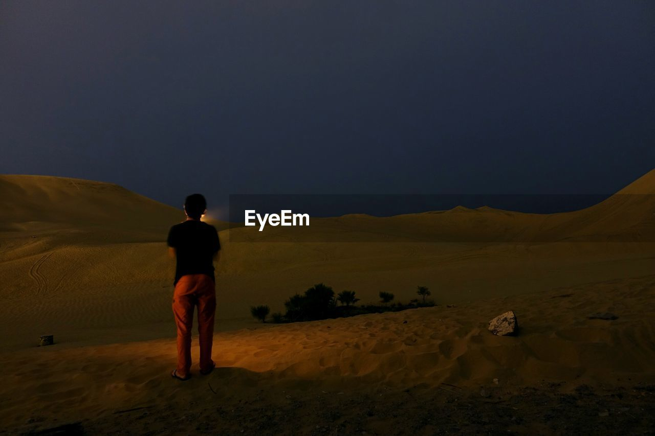 Rear View Of Man Standing On Landscape At Night