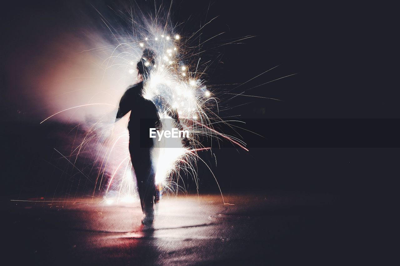 Blur Image Of Silhouette Person Walking By Firework Display On Road At Night
