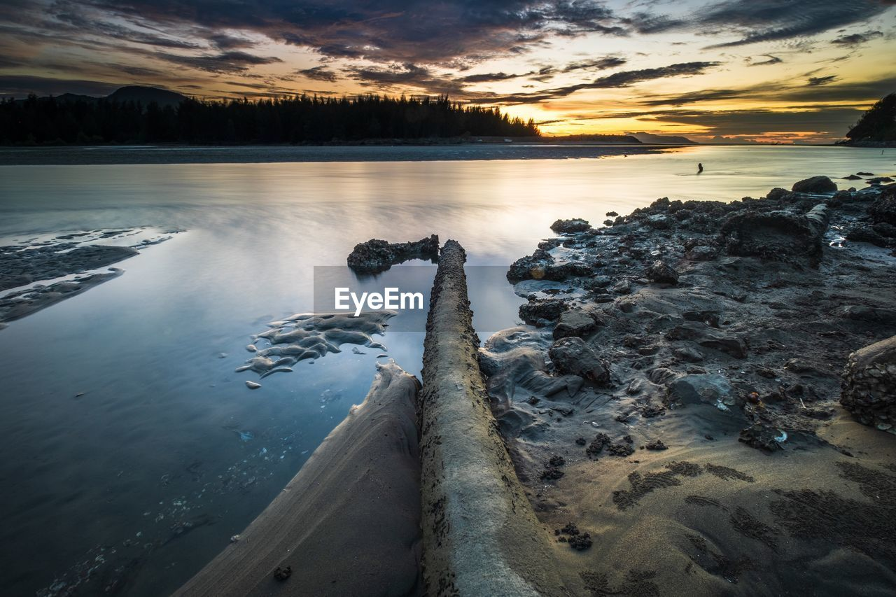 water, scenics - nature, beauty in nature, sunset, sky, tranquil scene, tranquility, cloud - sky, nature, non-urban scene, idyllic, no people, rock, lake, tree, solid, land, reflection, outdoors, driftwood, flowing water