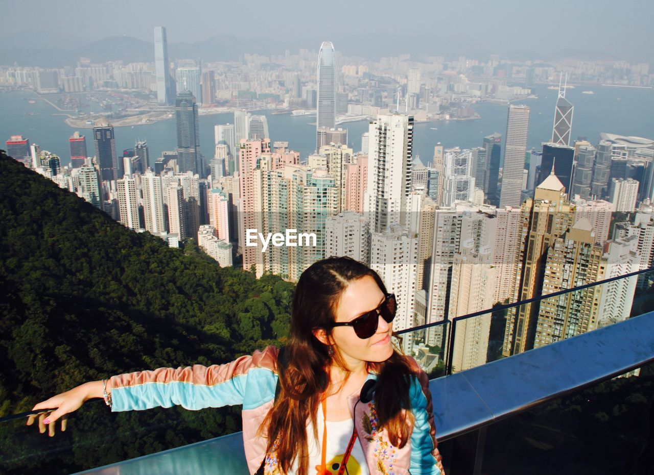 High Angle View Of Woman Against Skyscrapers At Victoria Harbour