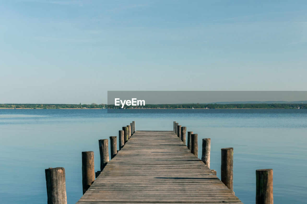 wood - material, water, sky, pier, direction, tranquility, sea, beauty in nature, the way forward, scenics - nature, jetty, tranquil scene, nature, no people, day, clear sky, idyllic, post, copy space, outdoors, diminishing perspective, wooden post, wood paneling, wood, long