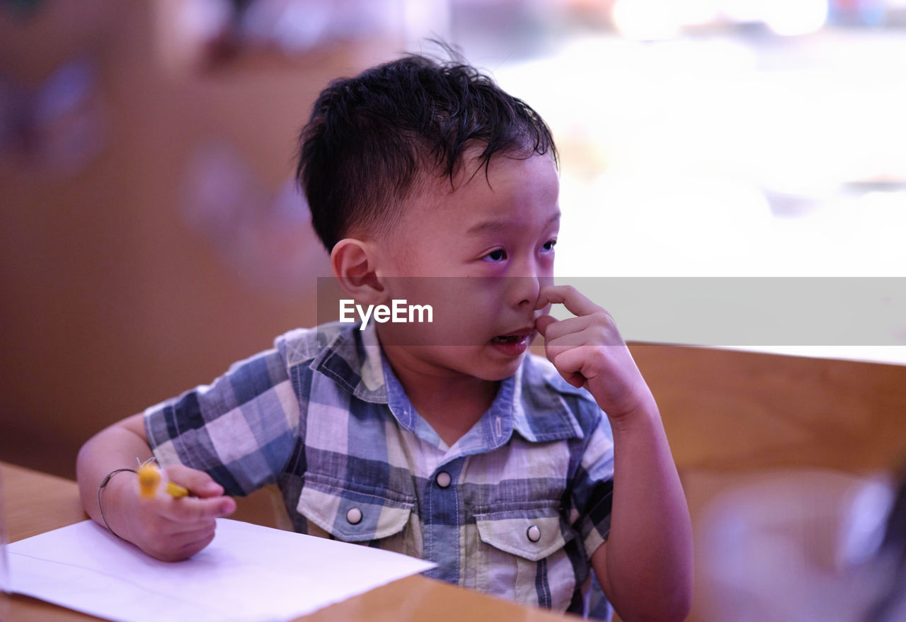 Cute boy looking away while sitting by table
