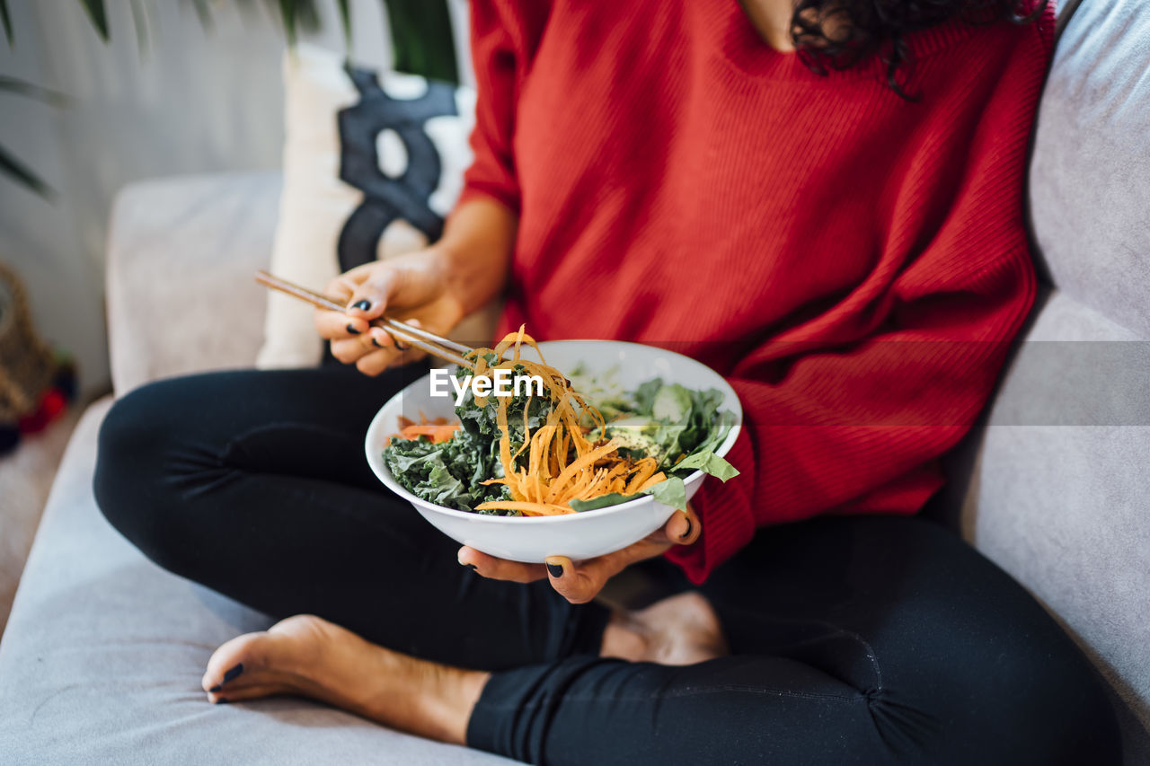 MIDSECTION OF WOMAN SITTING ON TABLE IN BOWL