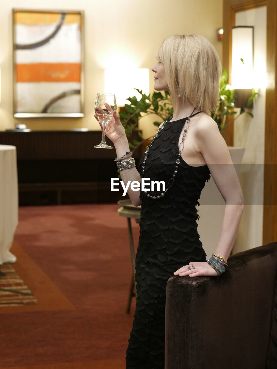 one person, three quarter length, rear view, alcohol, drink, real people, lifestyles, holding, young women, leisure activity, young adult, fashion, indoors, food and drink, drinking glass, women, blond hair, standing, night, people
