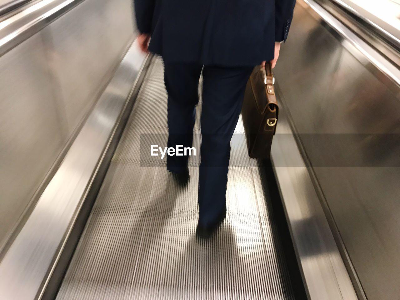 Blurred motion of people walking on escalator