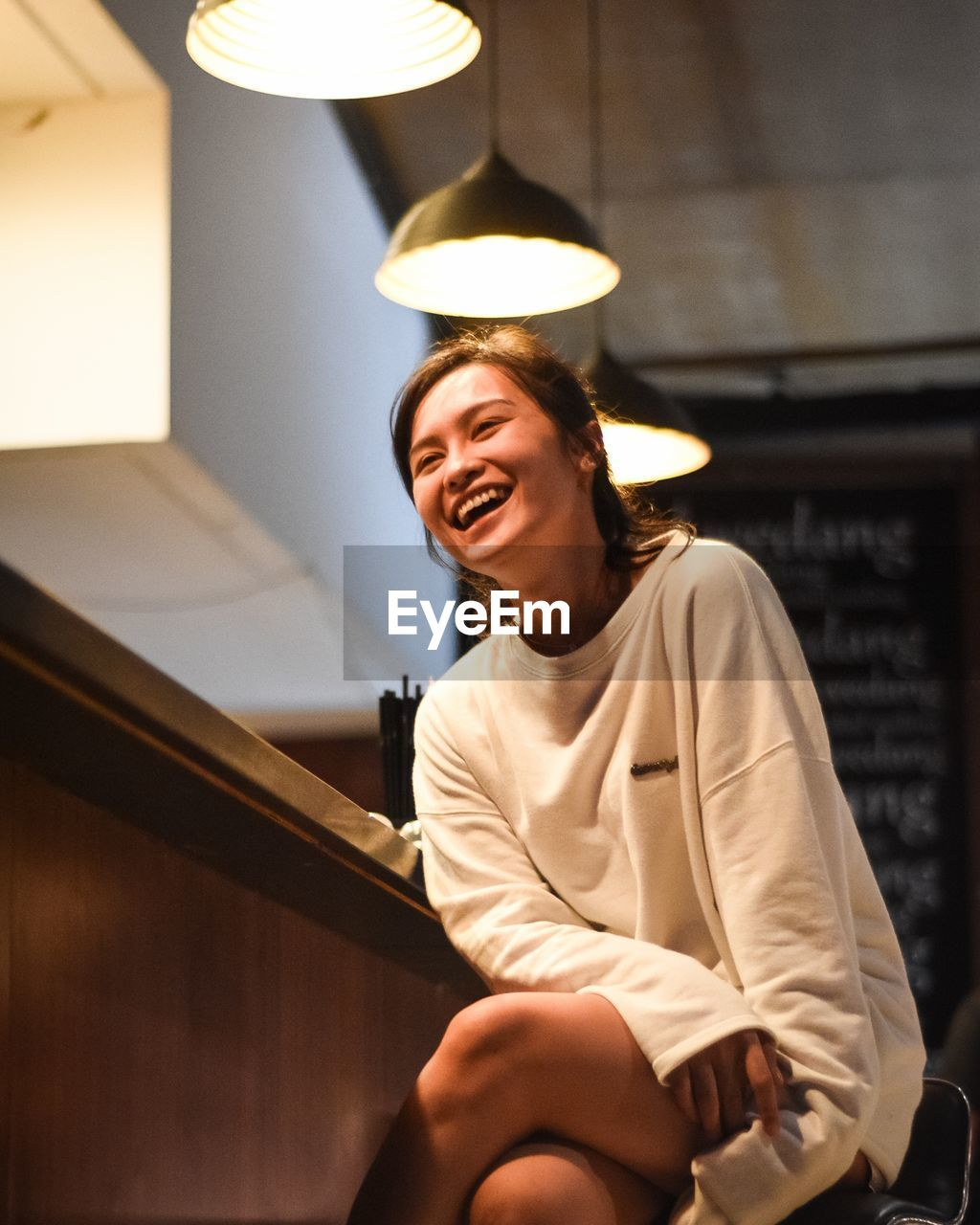 Young Woman Smiling While Sitting In Illuminated Cafe