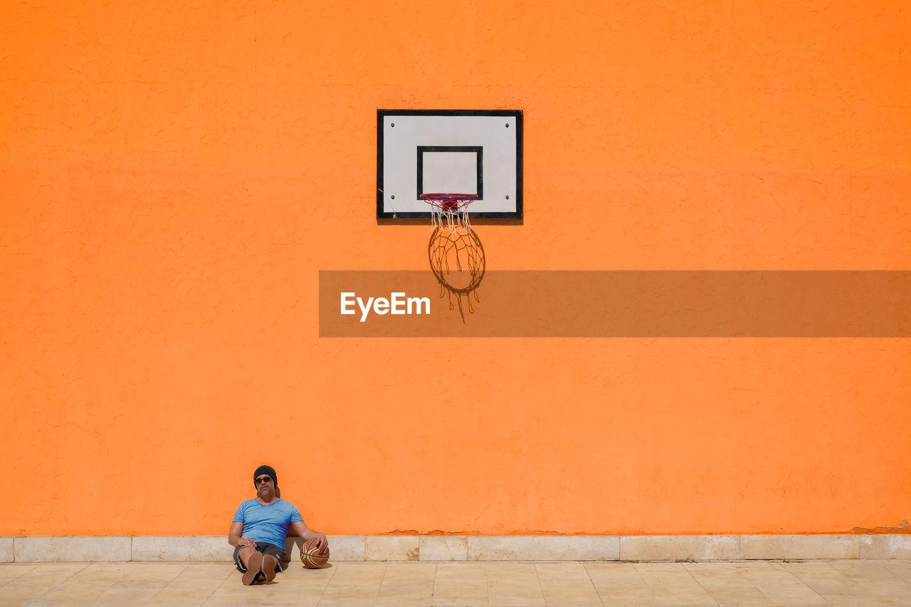 Man sitting on basketball court against orange wall