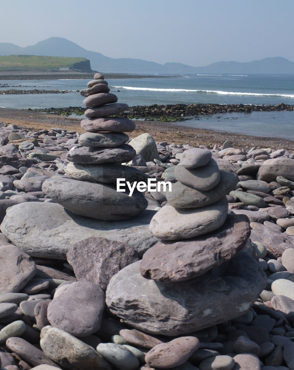 Stacked stones at beach against clear sky during sunny day