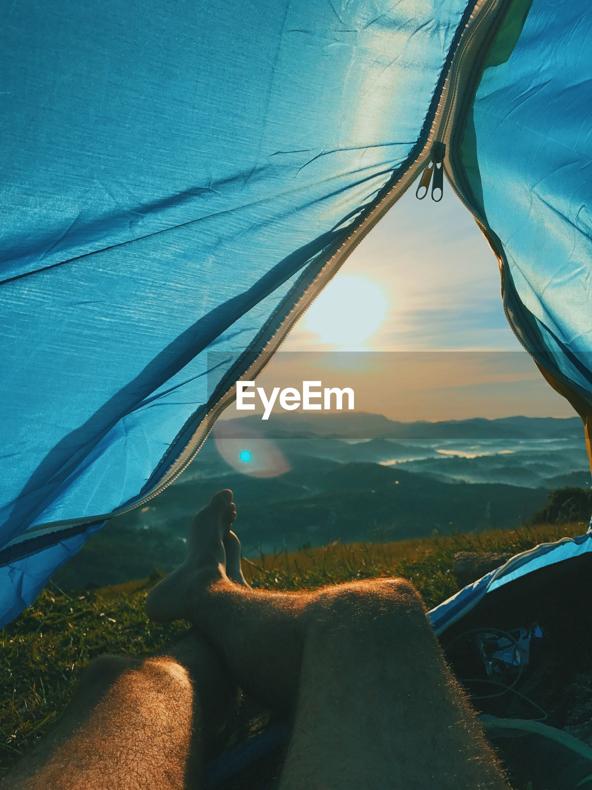 Low section of man relaxing in tent at sunset