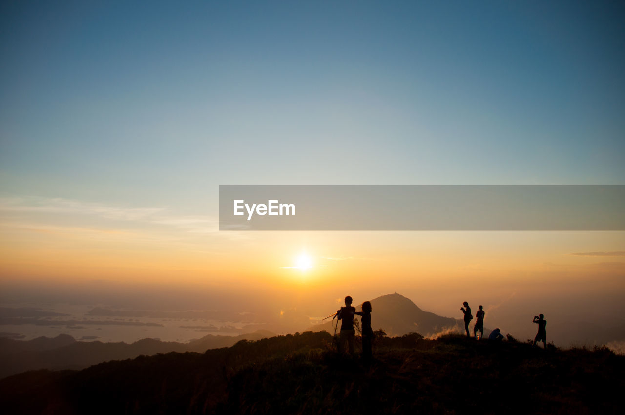 sunset, real people, nature, orange color, lifestyles, men, silhouette, leisure activity, scenics, sun, beauty in nature, sky, women, outdoors, medium group of people, standing, sunlight, tranquility, togetherness, hiking, mountain, adventure, photographing, landscape, camera - photographic equipment, photography themes, tree, friendship, day, people