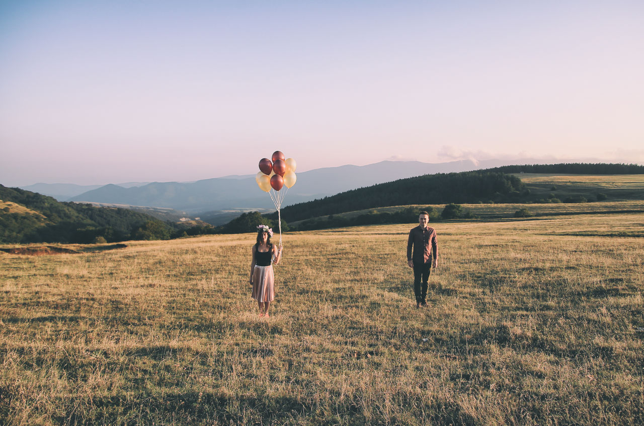 Girlfriend Holding Balloons While Boyfriend Standing On Grassy Field Against Sky During Sunset
