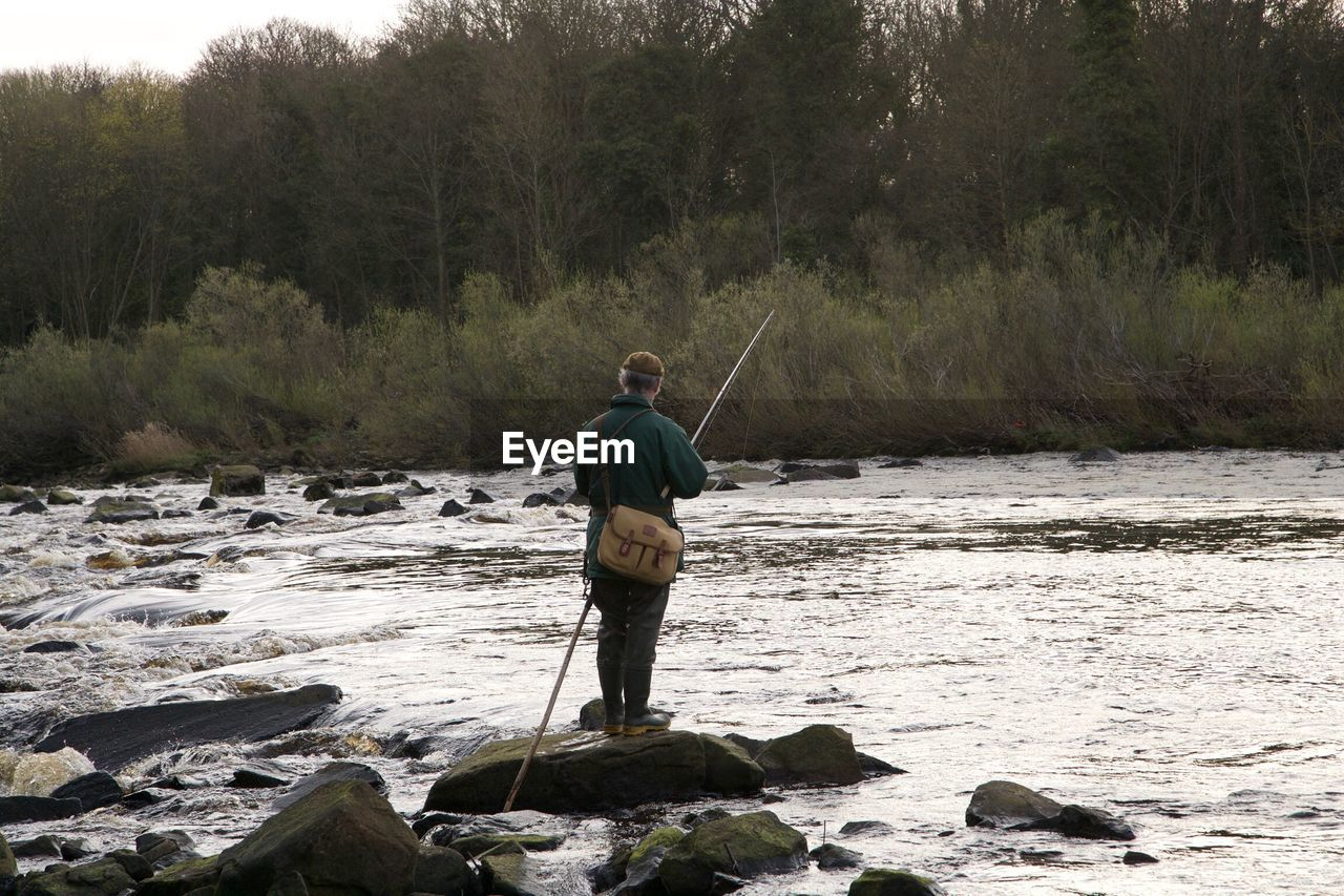 Rear view of man fishing in river