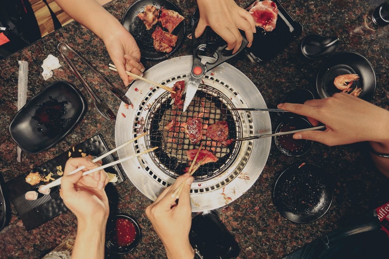Cropped Friends Preparing Meat On Barbecue