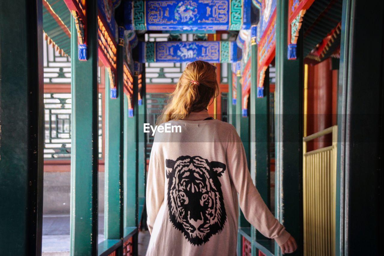 Rear View Of Woman Walking In Corridor Of Temple
