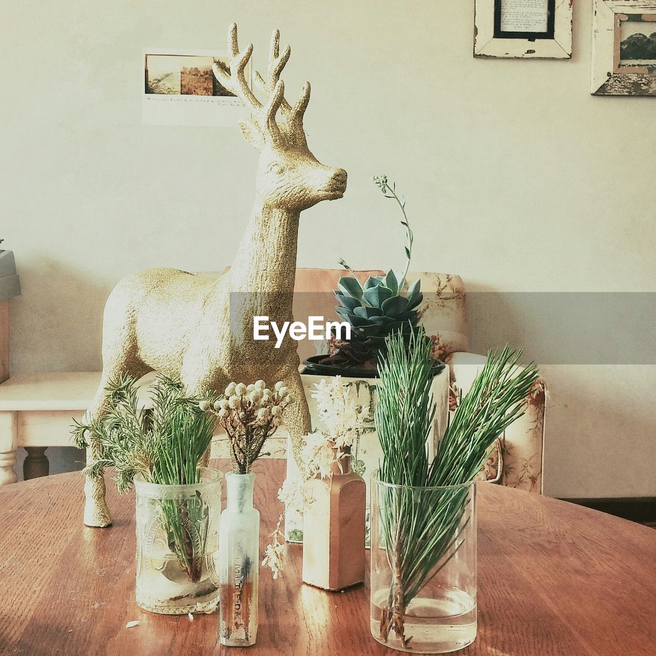 Reindeer Statue Amidst Plant Vases On Coffee Table In Living Room