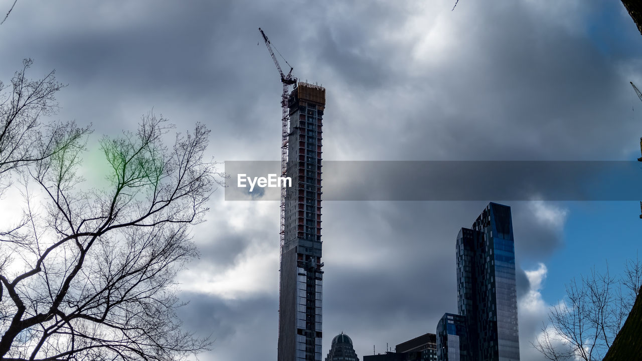 cloud - sky, sky, architecture, built structure, building exterior, low angle view, crane - construction machinery, tree, nature, construction industry, bare tree, industry, no people, machinery, development, construction site, tall - high, building, day, outdoors, office building exterior, skyscraper, construction equipment