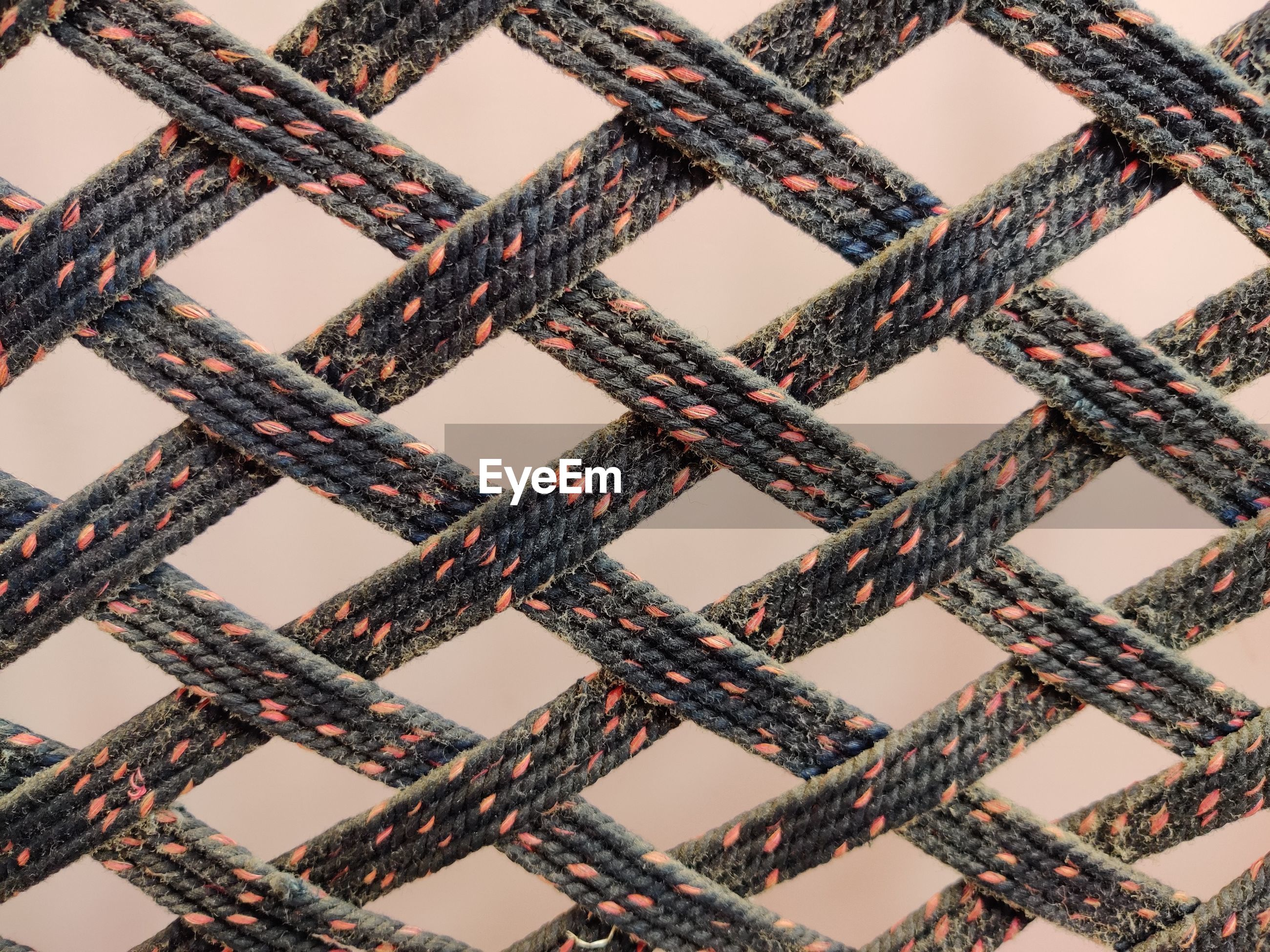 Full frame of woven fabric against wall