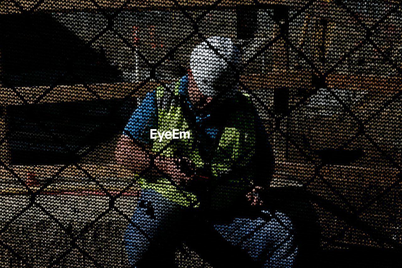 Construction worker seen through chainlink fence