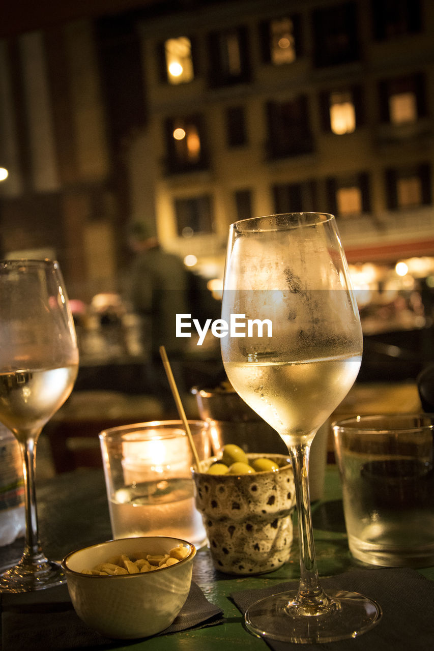 food and drink, refreshment, drink, alcohol, glass, table, wineglass, wine, focus on foreground, freshness, restaurant, business, food, drinking glass, indoors, incidental people, glass - material, transparent, household equipment, illuminated
