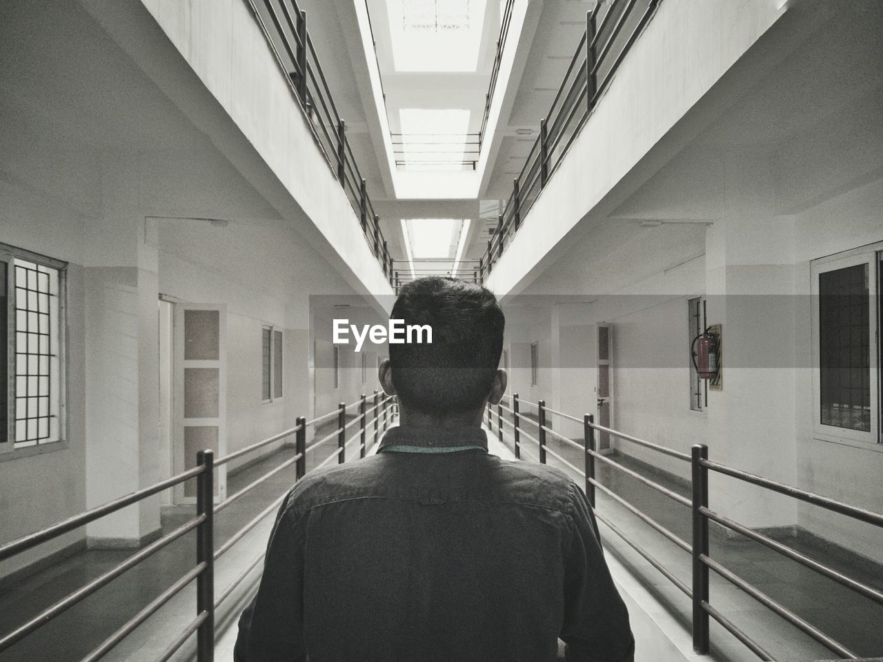 Rear View Of Man Standing In Prison