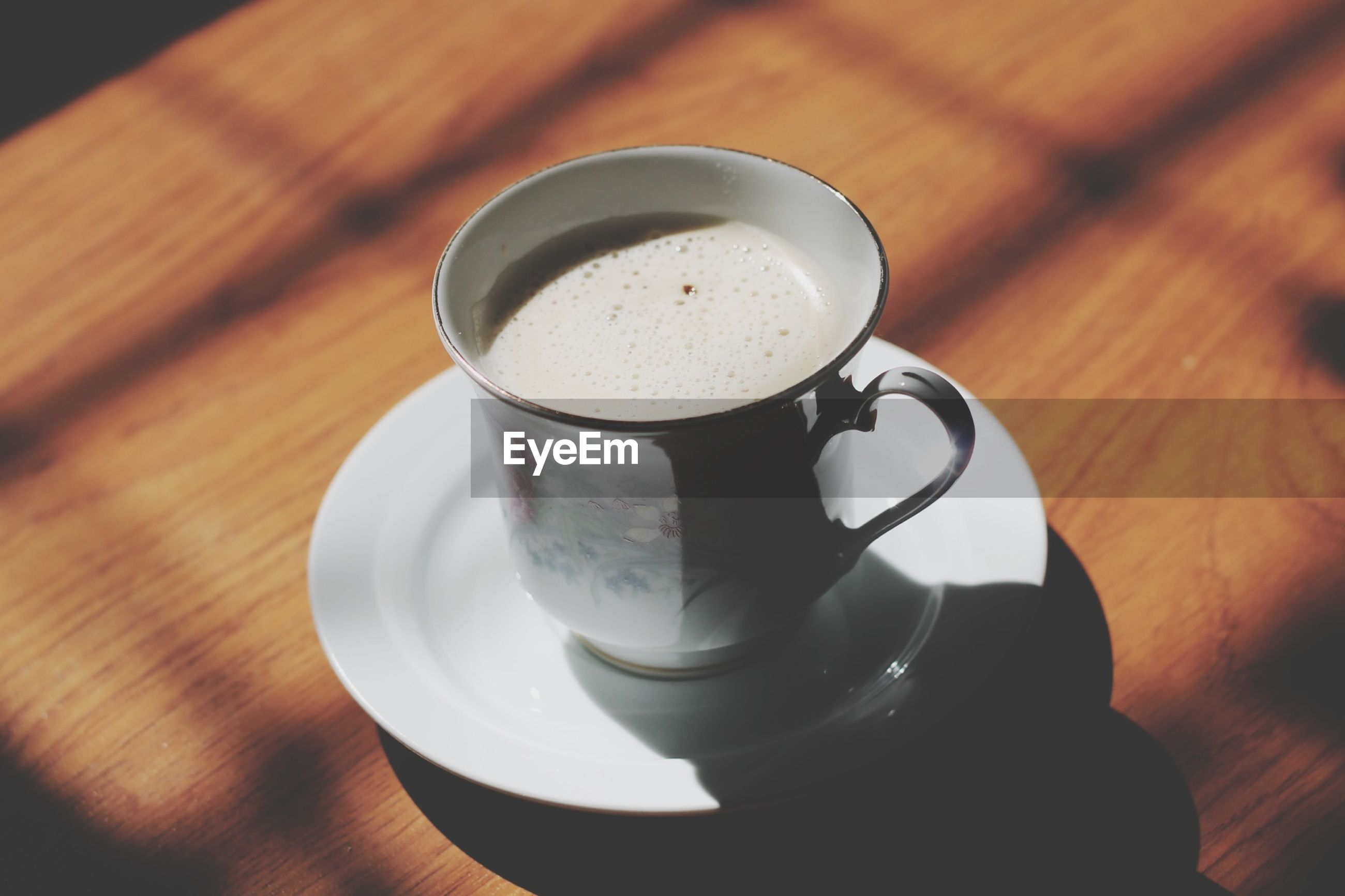 drink, food and drink, coffee cup, refreshment, table, indoors, coffee - drink, saucer, still life, freshness, coffee, cup, frothy drink, cappuccino, wood - material, close-up, spoon, beverage, high angle view, wooden
