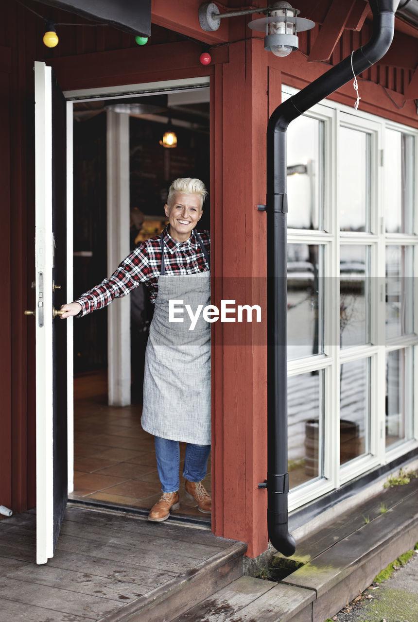 WOMAN STANDING BY DOOR OF BUILDING