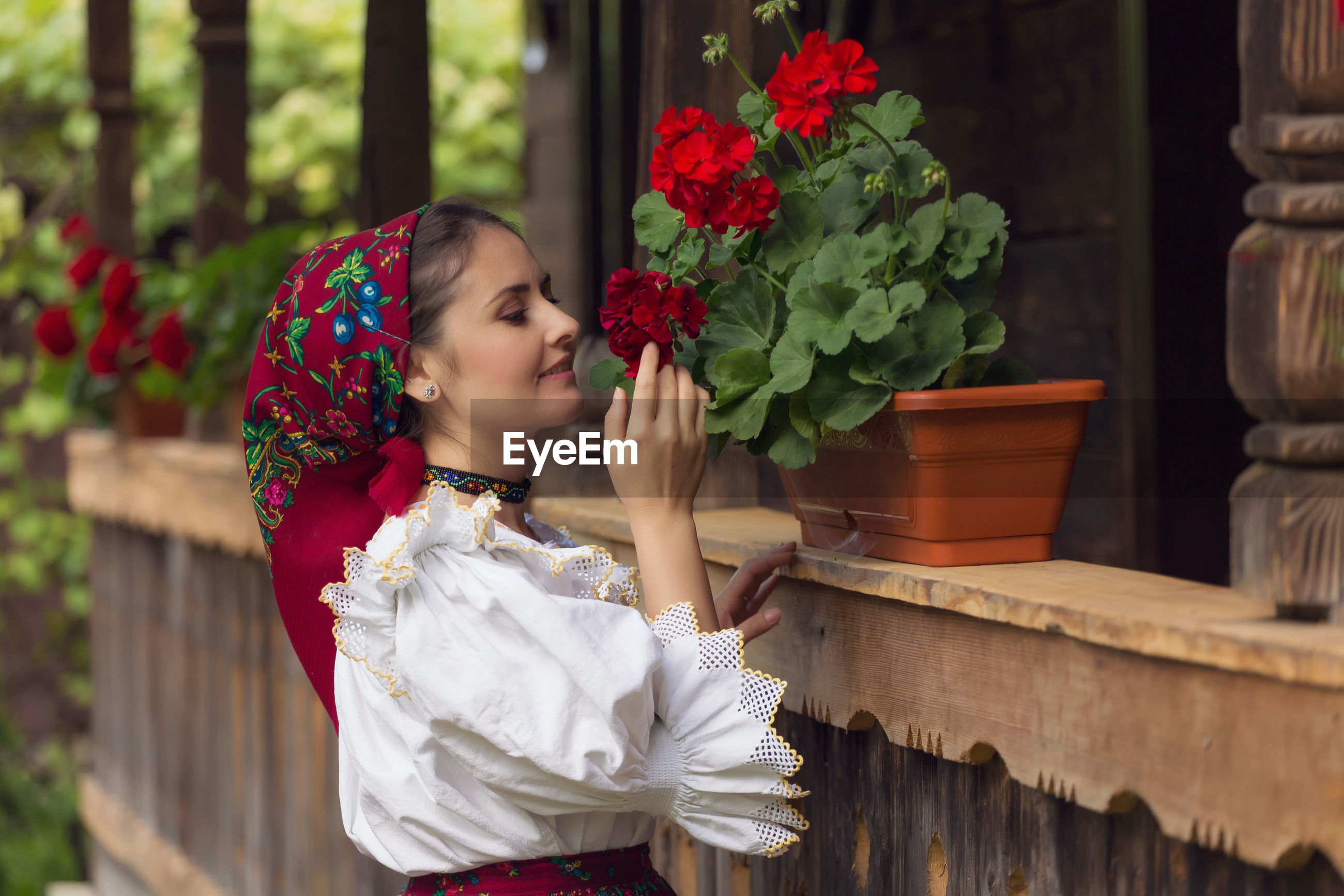 Beautiful young woman in romanian clothing smelling flowers at yard