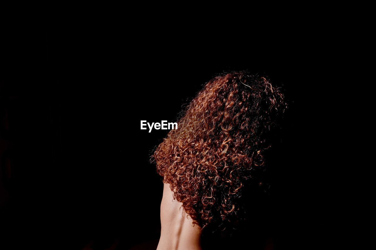 studio shot, black background, one person, human body part, indoors, body part, copy space, headshot, hair, hairstyle, portrait, human hair, curly hair, adult, women, close-up, young adult, human hand, hand, dark, human face, obscured face