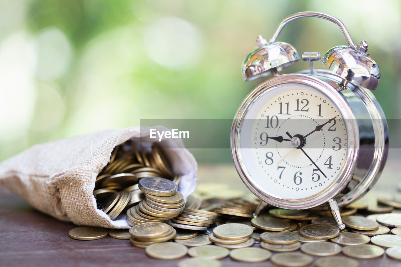 clock, alarm clock, time, number, coin, still life, finance, large group of objects, no people, wealth, savings, focus on foreground, close-up, stack, accuracy, clock face, business, metal, investment, table, silver colored
