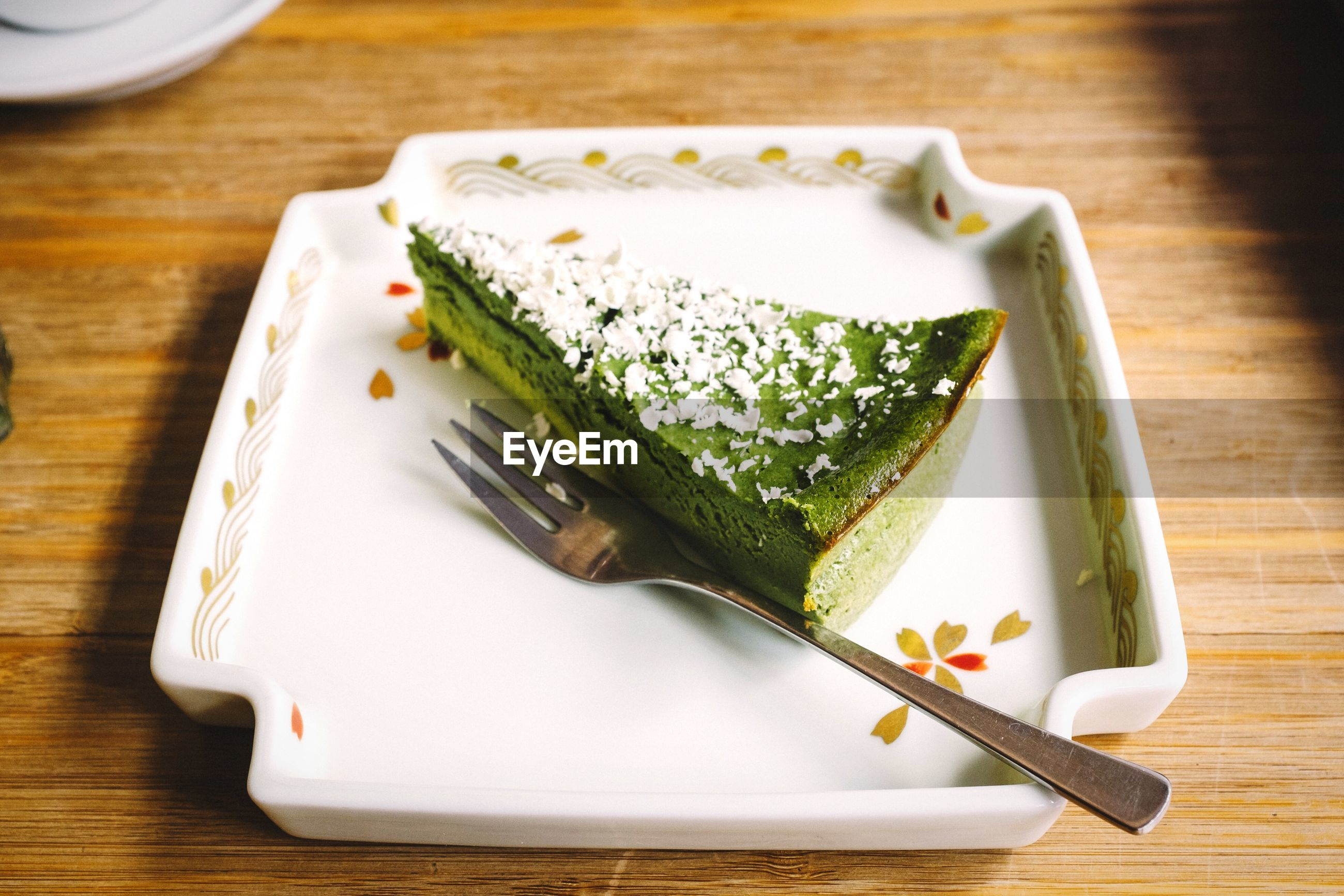 High angle view of green tea cheese cake in plate on table