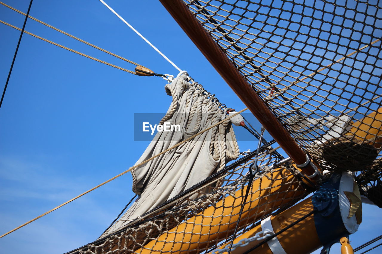 low angle view, sky, rope, no people, nautical vessel, day, nature, sailboat, mode of transportation, sunlight, transportation, outdoors, ship, blue, netting, protection, pattern, metal, fishing net, architecture, rigging, fishing industry
