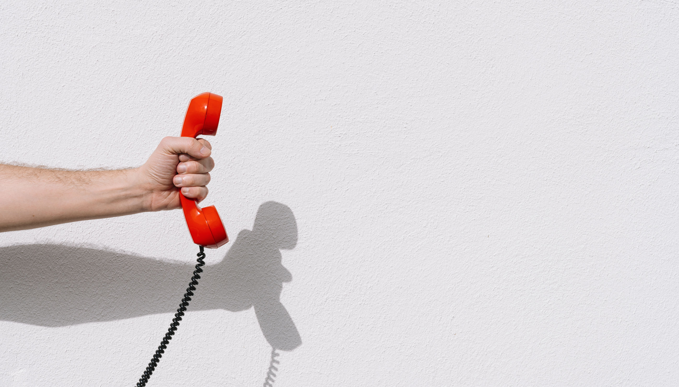 Cropped hand of man holding red telephone receiver against white wall