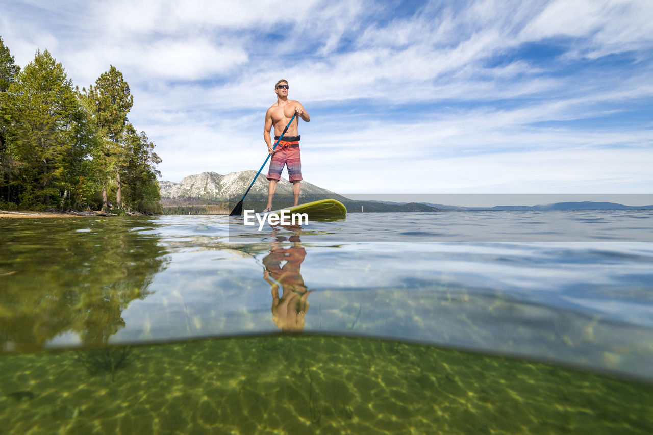 MAN SURFING IN WATER AGAINST SEA