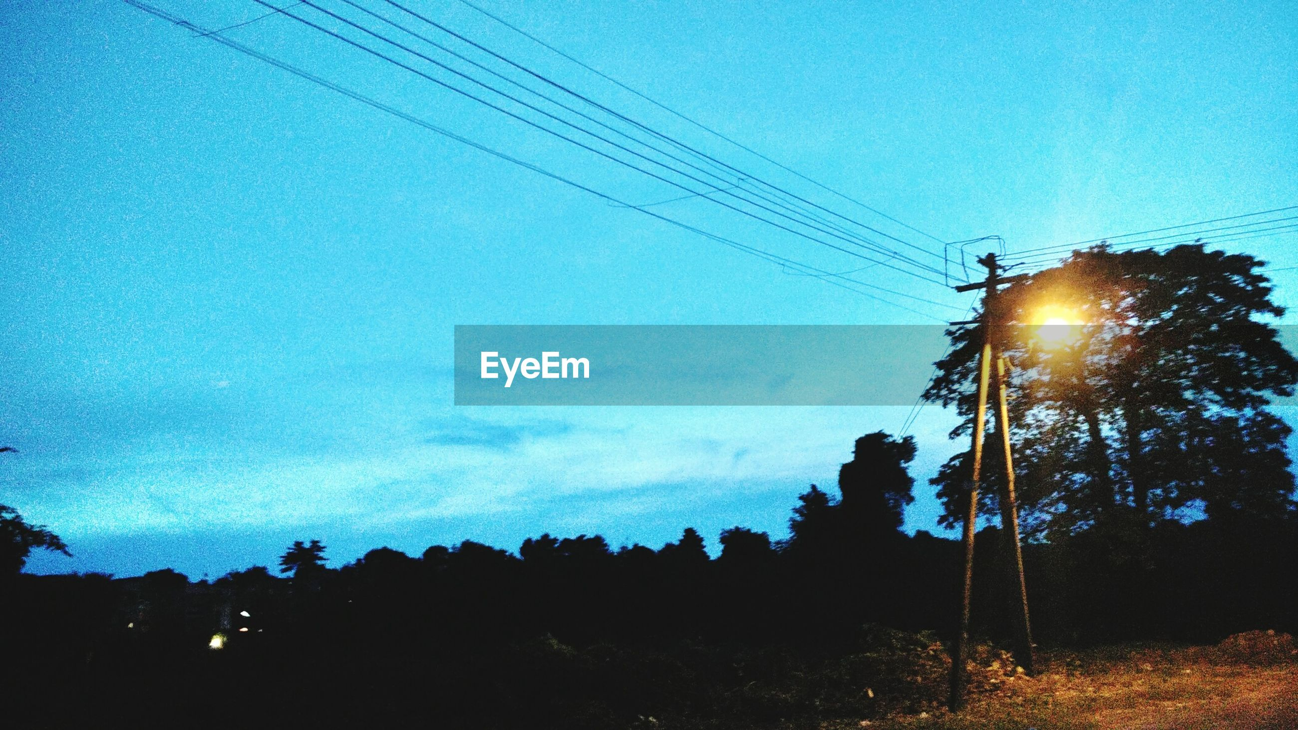 power line, electricity pylon, silhouette, electricity, low angle view, cable, power supply, sky, tree, street light, technology, blue, fuel and power generation, sun, lighting equipment, power cable, clear sky, connection, dusk, sunlight