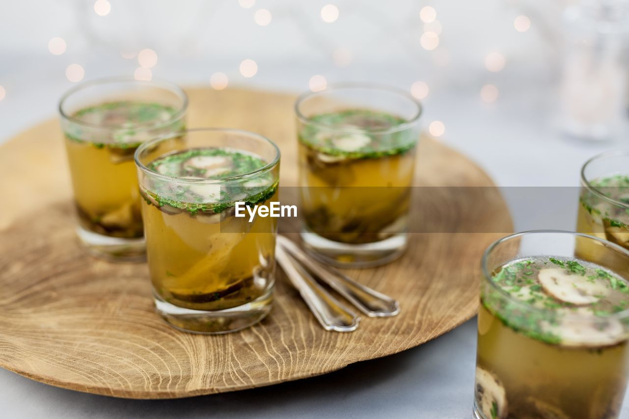 food and drink, table, drink, freshness, refreshment, household equipment, food, drinking glass, glass, close-up, indoors, still life, no people, ready-to-eat, focus on foreground, serving size, healthy eating, eating utensil, kitchen utensil, wood - material, herb, mint leaf - culinary, tray