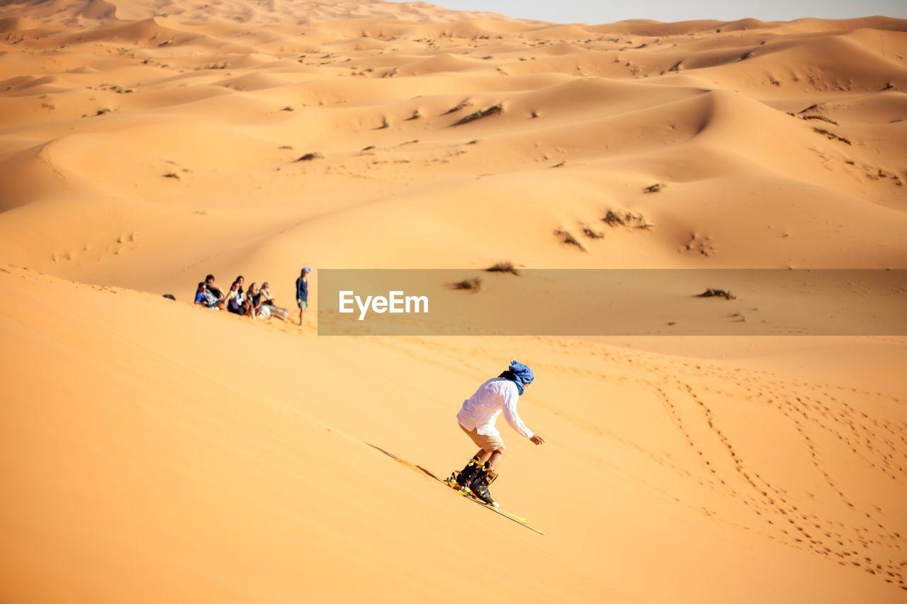 Person Sandboarding In Desert Against Clear Sky