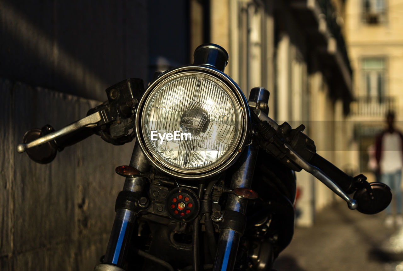 focus on foreground, architecture, metal, mode of transportation, land vehicle, transportation, headlight, bicycle, handlebar, motorcycle, city, day, close-up, travel, building exterior, no people, stationary, built structure, lighting equipment, outdoors, chrome