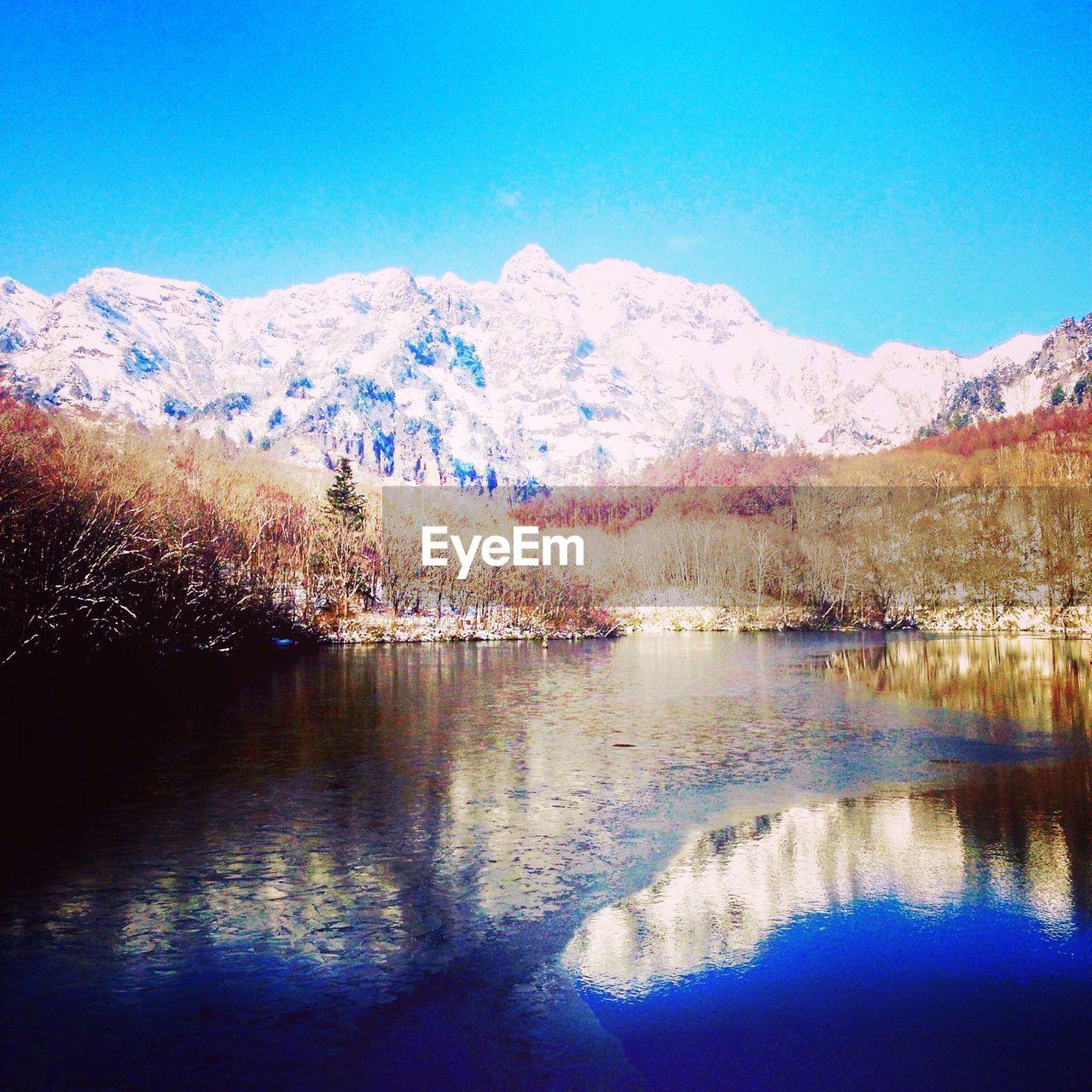 reflection, mountain, tranquil scene, scenics, lake, tranquility, beauty in nature, nature, water, no people, idyllic, outdoors, tree, day, mountain range, waterfront, blue, landscape, travel destinations, cold temperature, snow, sky, clear sky, wilderness area